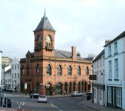Arts Center Downpatrick. This Venetian Gothic red brick building replaced the old Market House in 1892. It was built at the sole expence of John Mulholland (the first Lord Dunleath). It was designed by William Butt of Belfast. The tall clock tower is a distinctive feature.